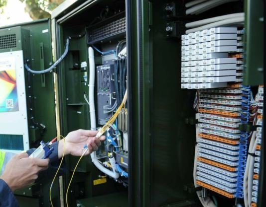 An telecommunications engineer working at a street cabinet